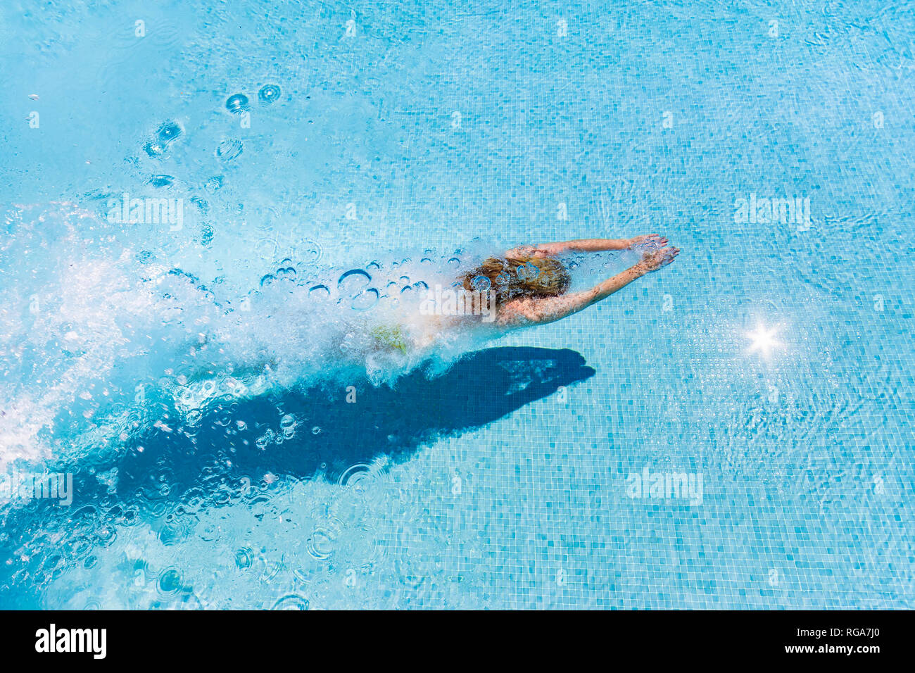 Spain, Málaga Province, Mondron,  woman diving into swimming pool creating bubbles - Stock Image