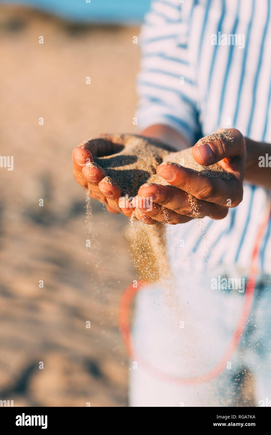 Woman on the beach letting sand trickling through her hands, close-up - Stock Image