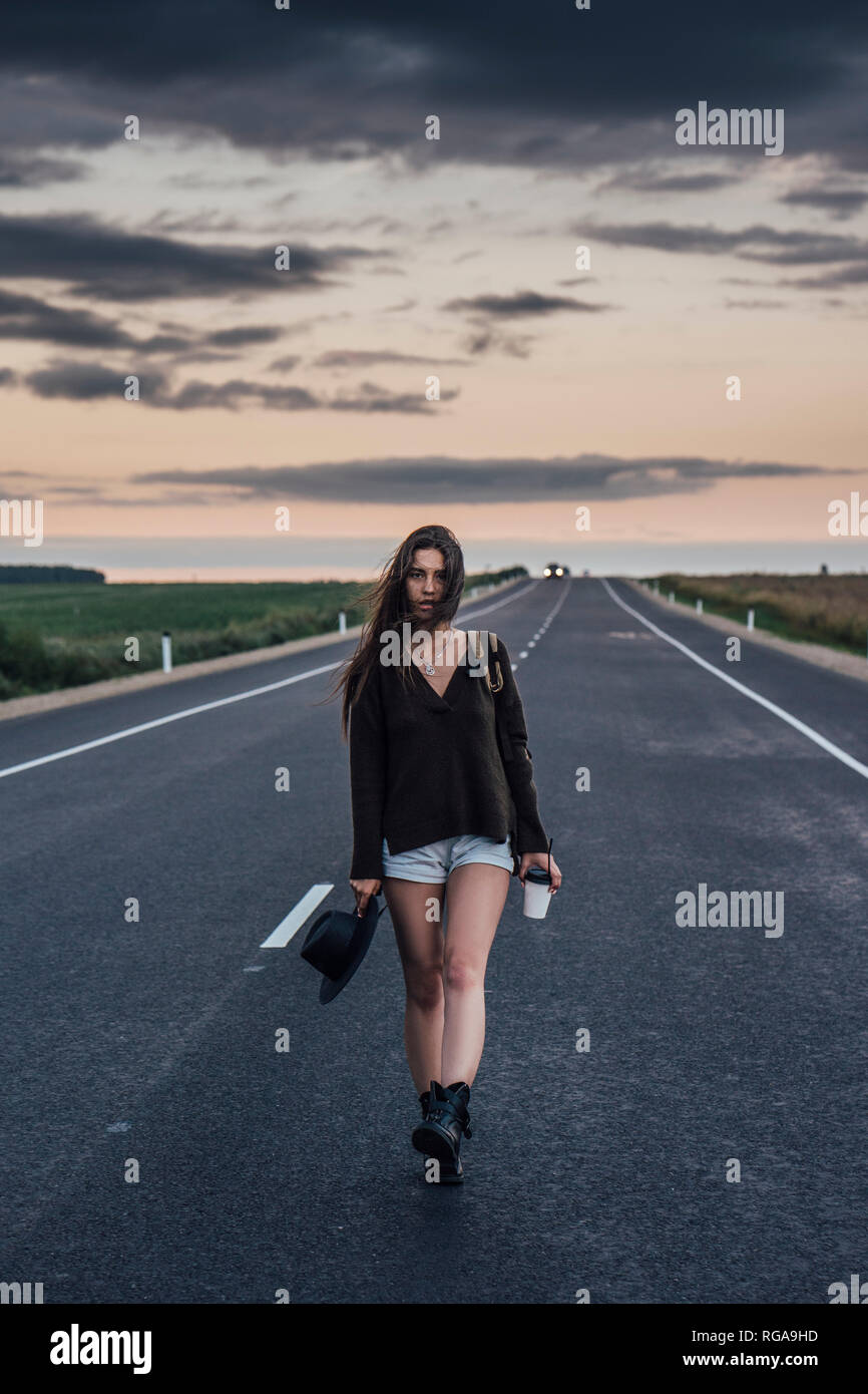 Portrait of hitchhiking young woman with backpack and beverage walking on lane at evening twilight Stock Photo