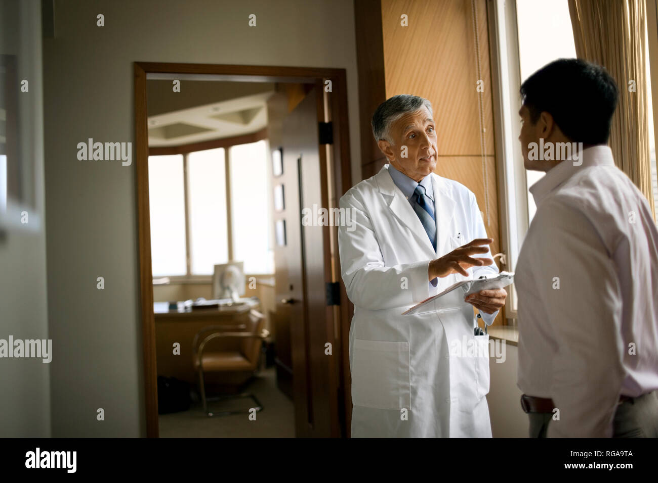 Friendly senior doctor consulting with a patient outside his office. - Stock Image