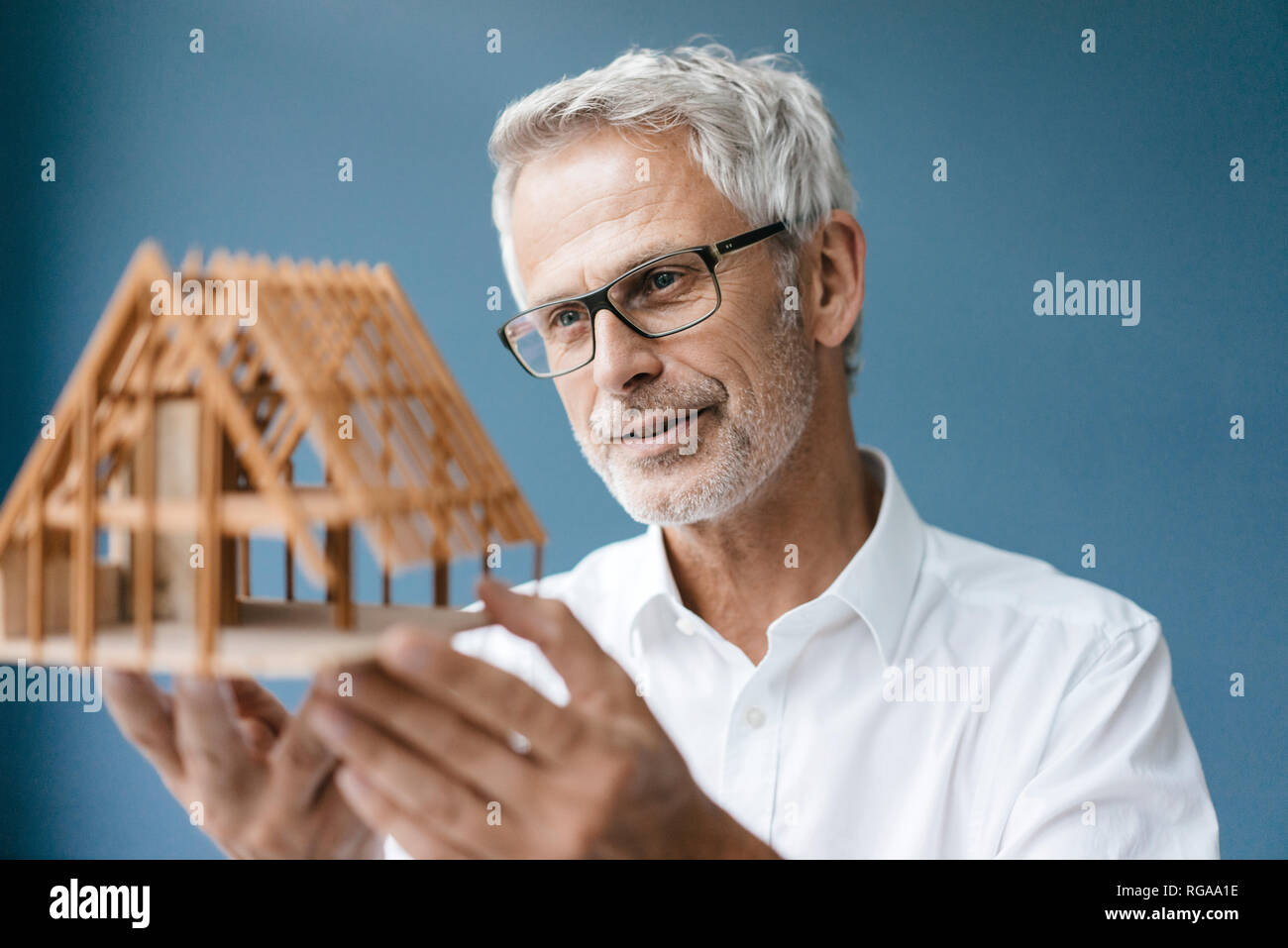 Successful architect looking at model of a house - Stock Image