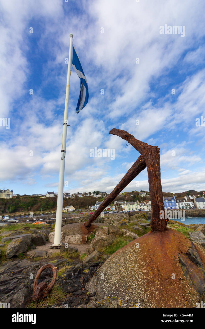 Scottish flag on a white flagpole and rusty boat anchor in Portpatrick harbor on an overcast day in Scotland, United Kingdom - Stock Image
