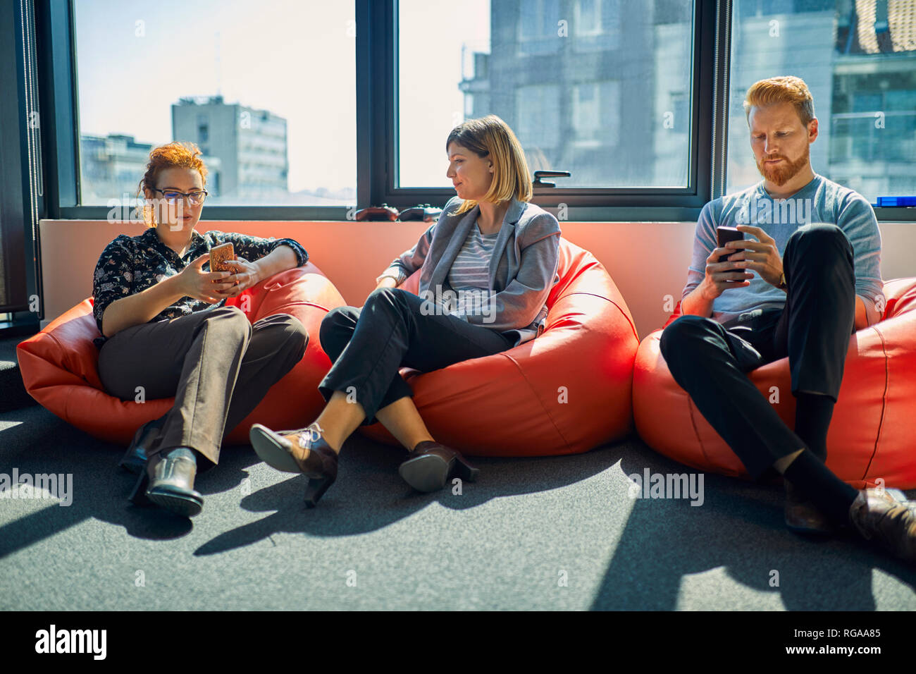 Colleagues with cell phones sitting in bean bags in office lounge - Stock Image