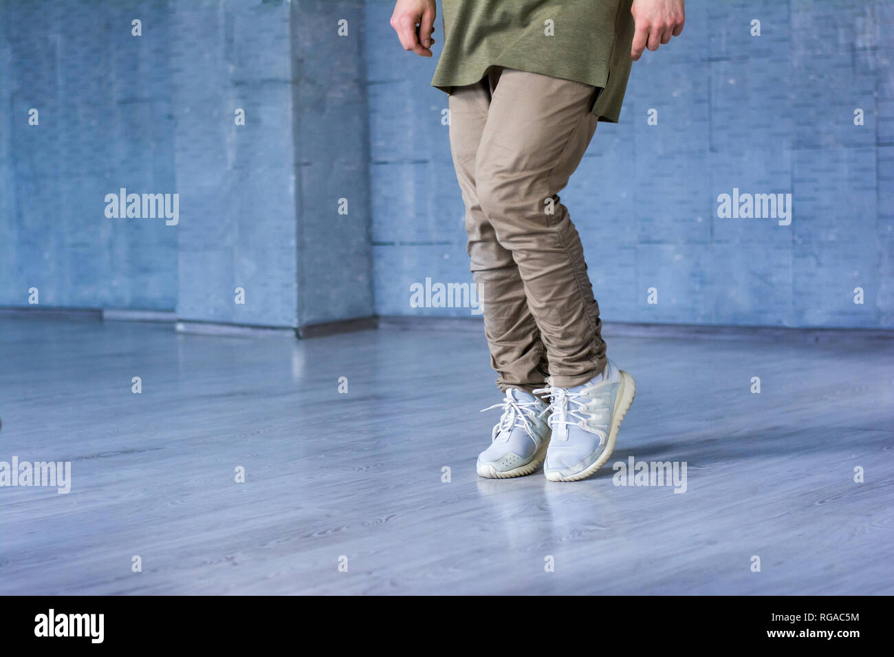 Dancer on grey background, cropped image. Hip-hop dancer wearing grey cotton trousers and sneakers on grey background. Sreet style dancing. - Stock Image