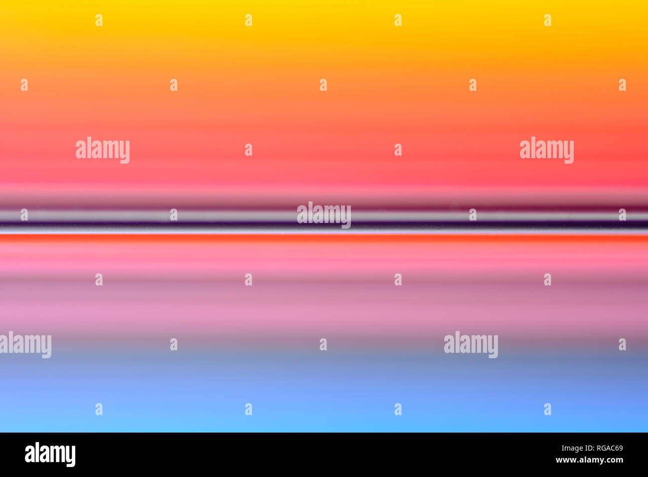 Colourful blurred spectrum made from an image of colored wooden sticks with a shallow depth of field  as a graphical resource / background / texture - Stock Image