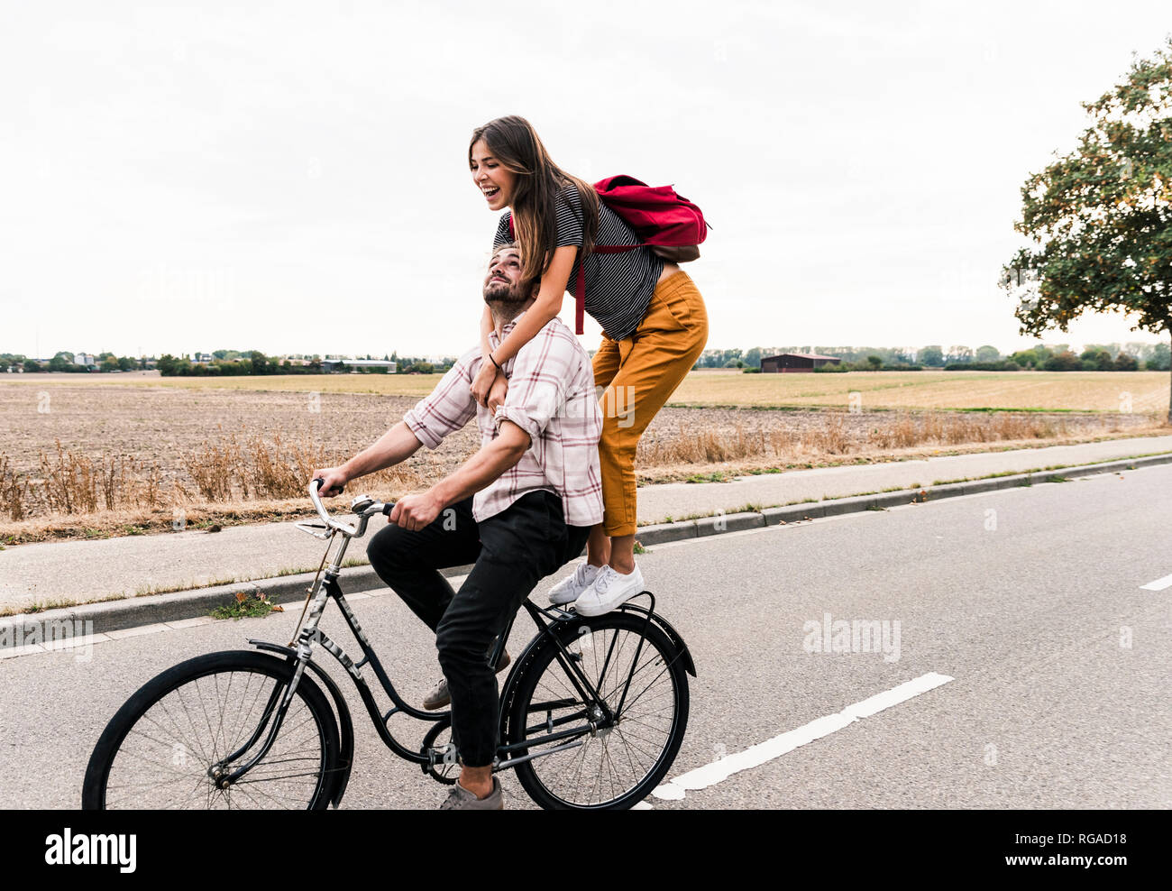 Happy young couple riding together on one bicycle on country road - Stock Image