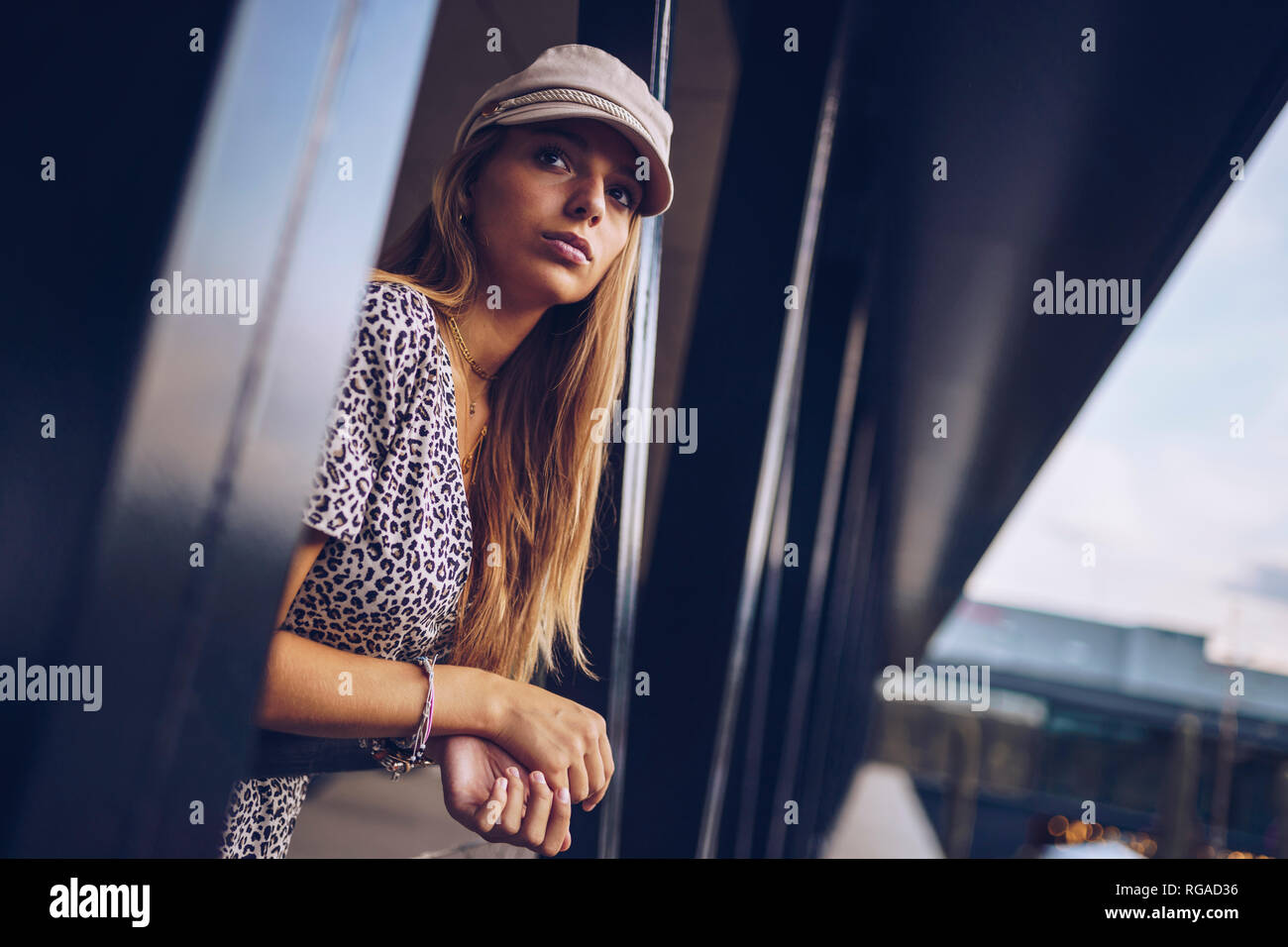 Attractive young woman in leopard print dress looking away Stock Photo