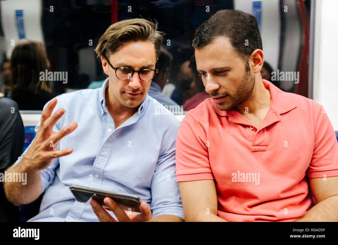 Portrait of two friends sharing cell phone in subway Stock Photo