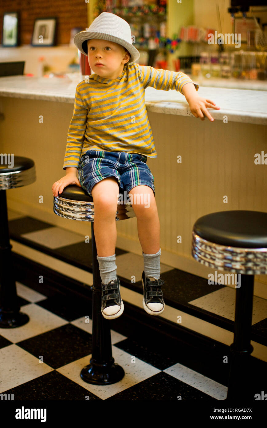 Young boy wearing a porkpie hat perches on a tall stool at a restaurant counter. - Stock Image