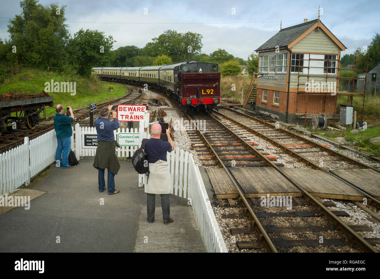 Train enthusiasts photograph a steam train of the South Devon Railway as it arrives at Ashburton Junction near Totnes, Devon - Stock Image
