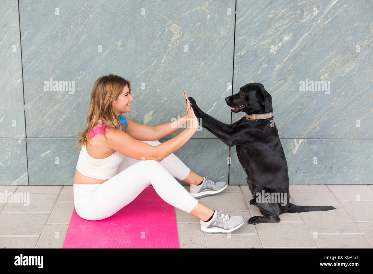 Young woman sitting on Yoga mat doing relaxation exercise with her black dog - Stock Image