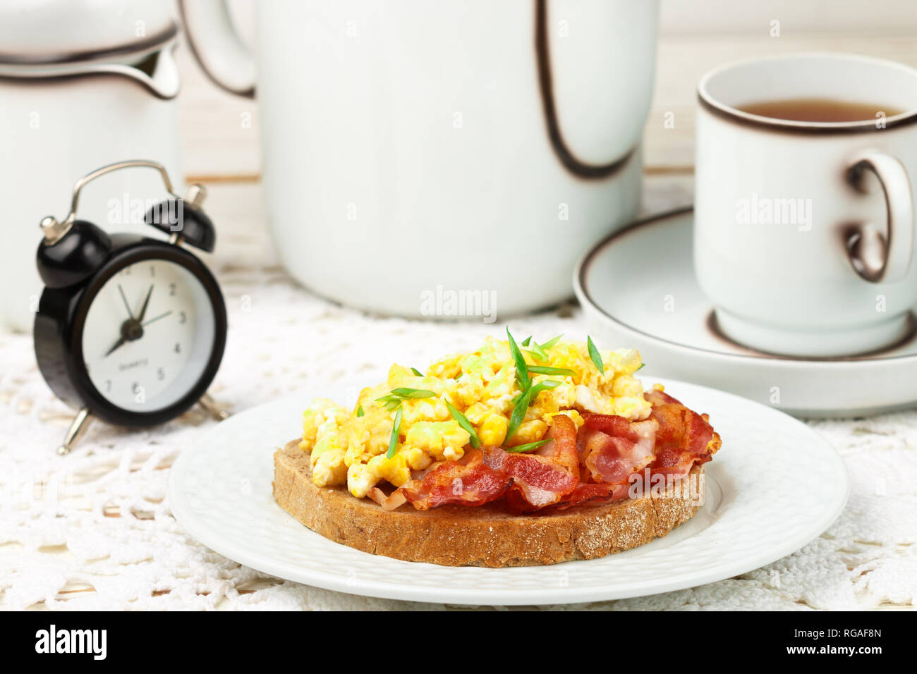 Bread toast with scrambled eggs, fried bacon and green onions.  Delicious breakfast. Brunch. Selective focus - Stock Image