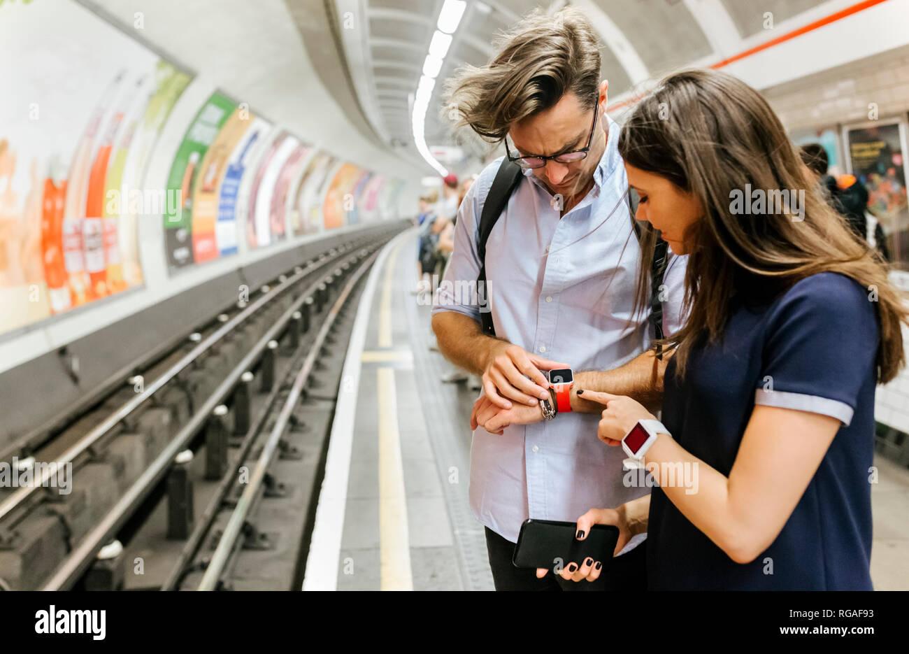 UK, London, couple waiting at   underground station platform looking at smartwatch - Stock Image