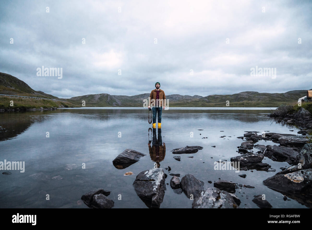 Young man standing ankle deep in water, holding camera - Stock Image