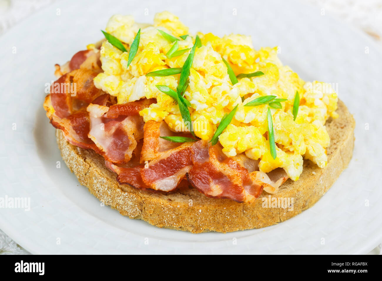 Bread toast with scrambled eggs, fried bacon and green onions close-up.  Delicious breakfast. Brunch. Selective focus - Stock Image