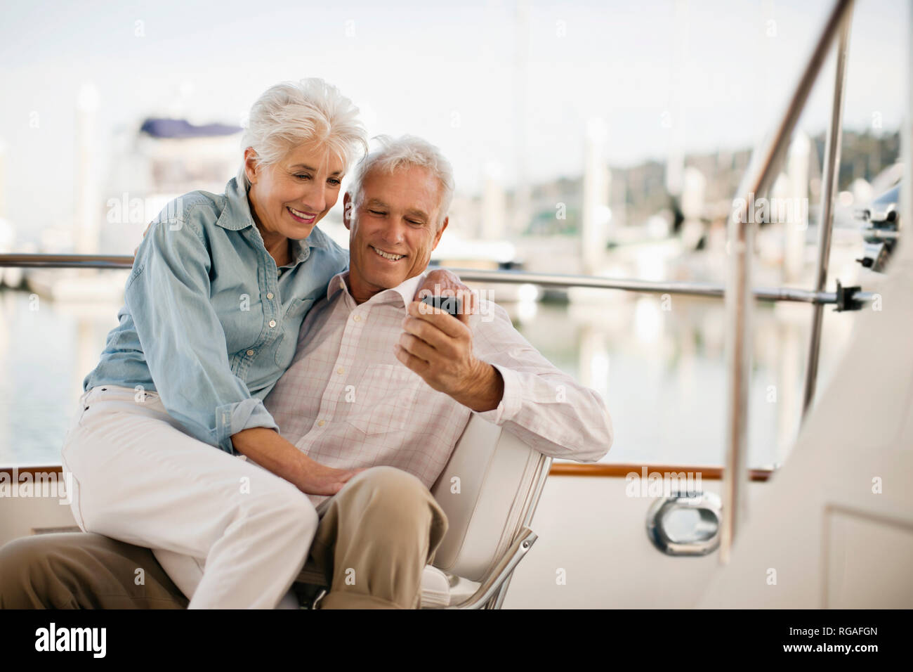 Senior woman sits on her husbands lap as he looks at the screen of his mobile phone. - Stock Image