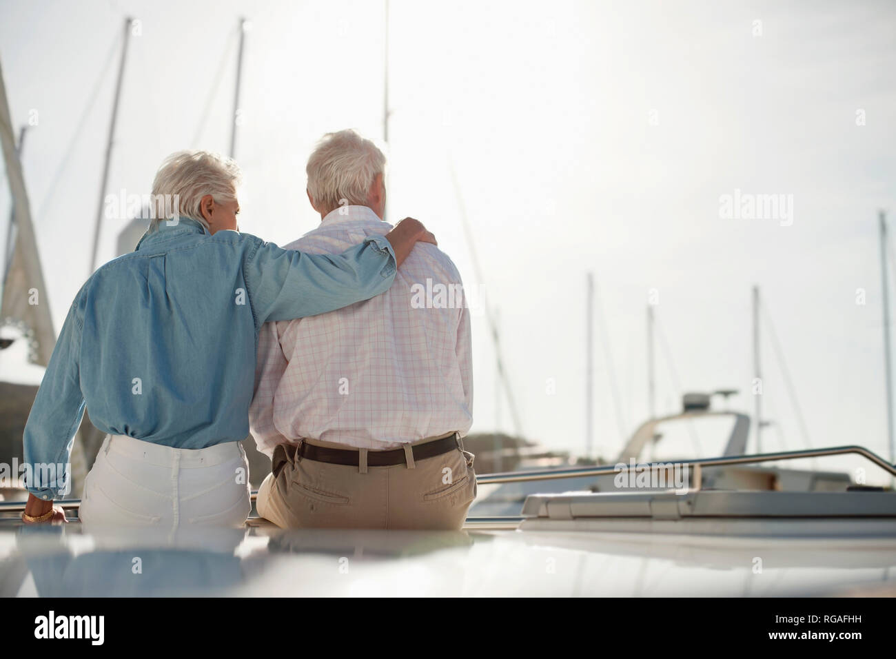 Senior woman puts her hand around her husband's shoulders as they sit on a boat looking out over the marina. - Stock Image