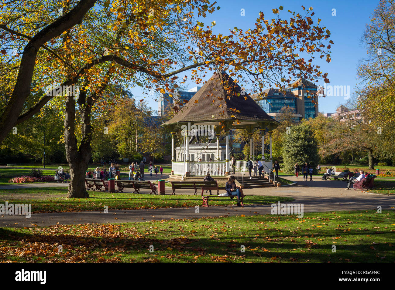People enjoy some late Autumn sunshine by the bandstand in Forbury Gardens, Reading, Berkshire - Stock Image