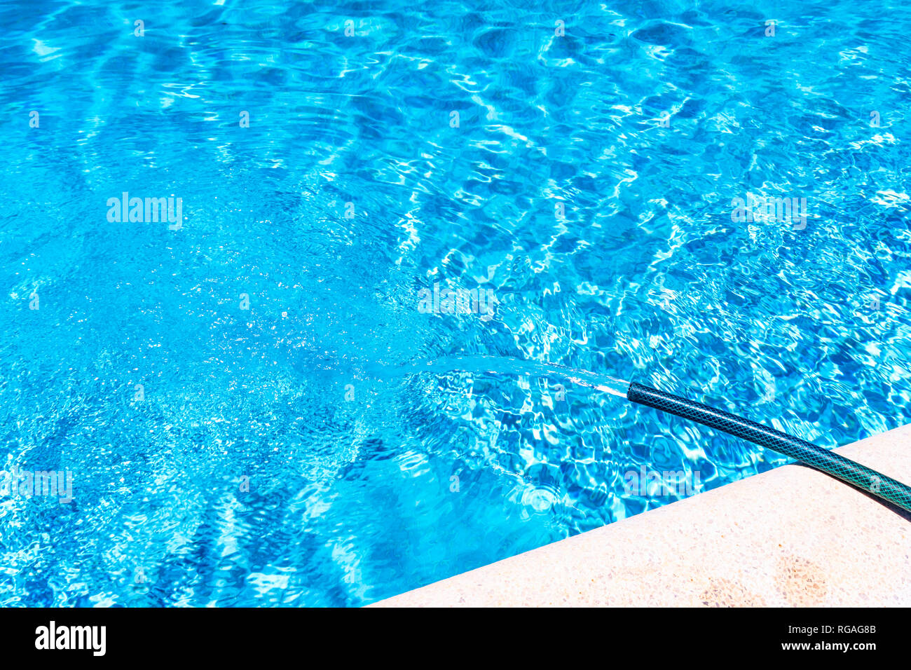 Spain, Andalucía, Málaga, Mondrón, swimming pool being filled by hosepipe - Stock Image