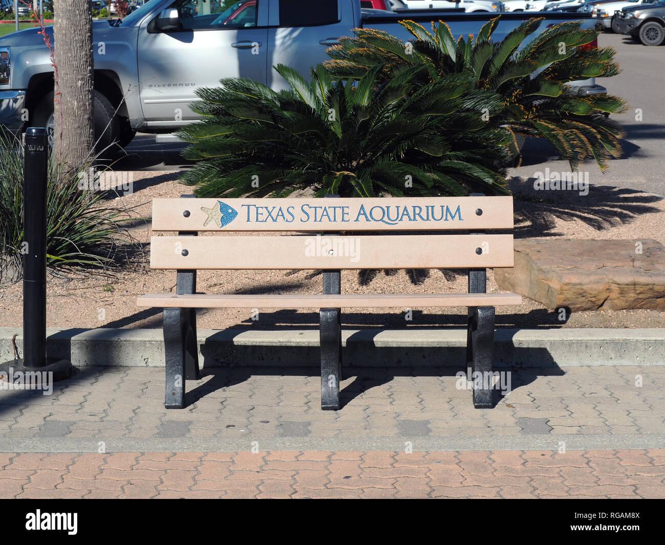A bench with the Texas State Aquarium logo on the aquarium property in Corpus Christi Texas USA. Stock Photo