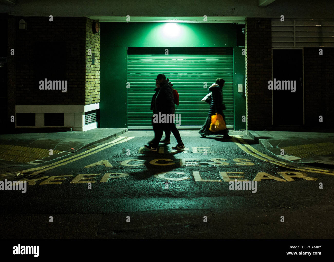 fire access keep clear, sinageon road infront of green steel roller shutter garage door Stock Photo