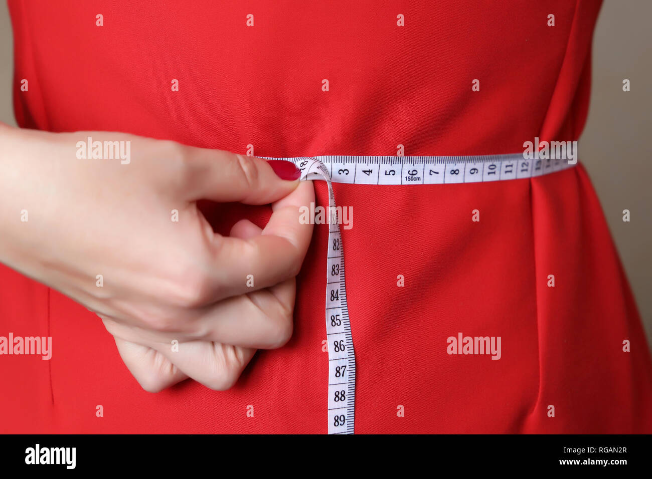 Girl in red dress with measuring tape around the waist. Weight loss, slimming, diet concept, body care, fitting clothes - Stock Image