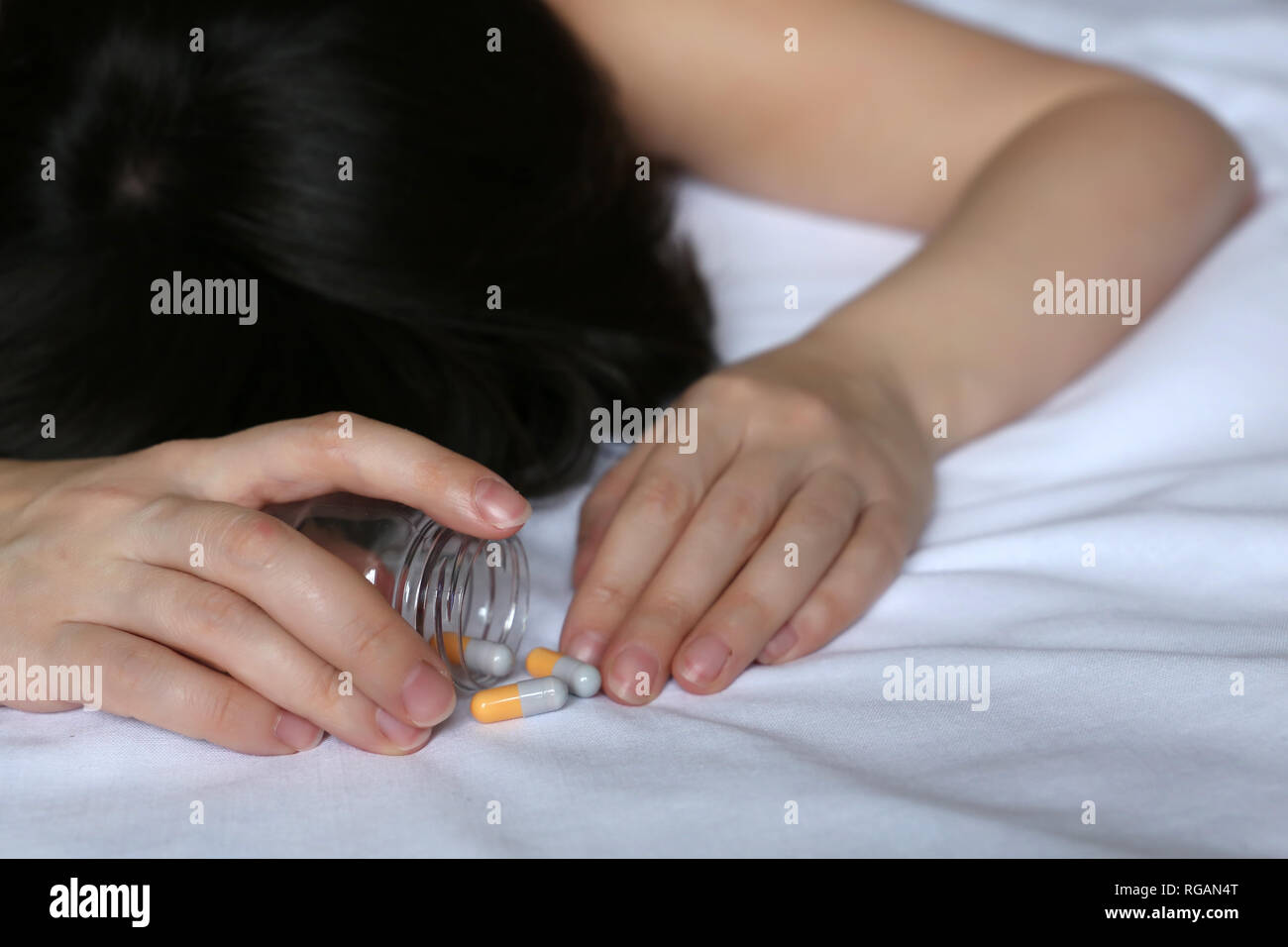 Girl lying on the bed with pills scattered. Concept of taking drugs, illness, sleeping pill, overdose or suicide - Stock Image