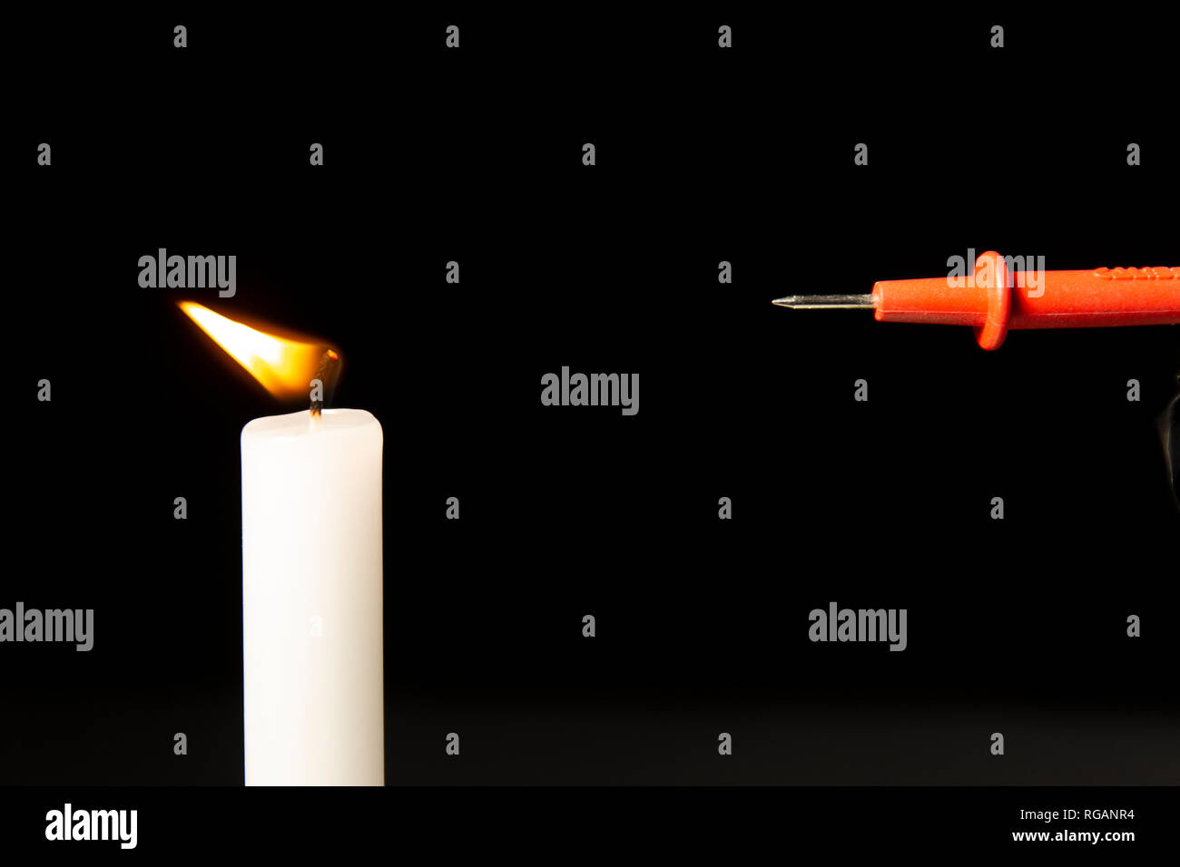 A static electricity charged metal tip bending a candle fire. - Stock Image