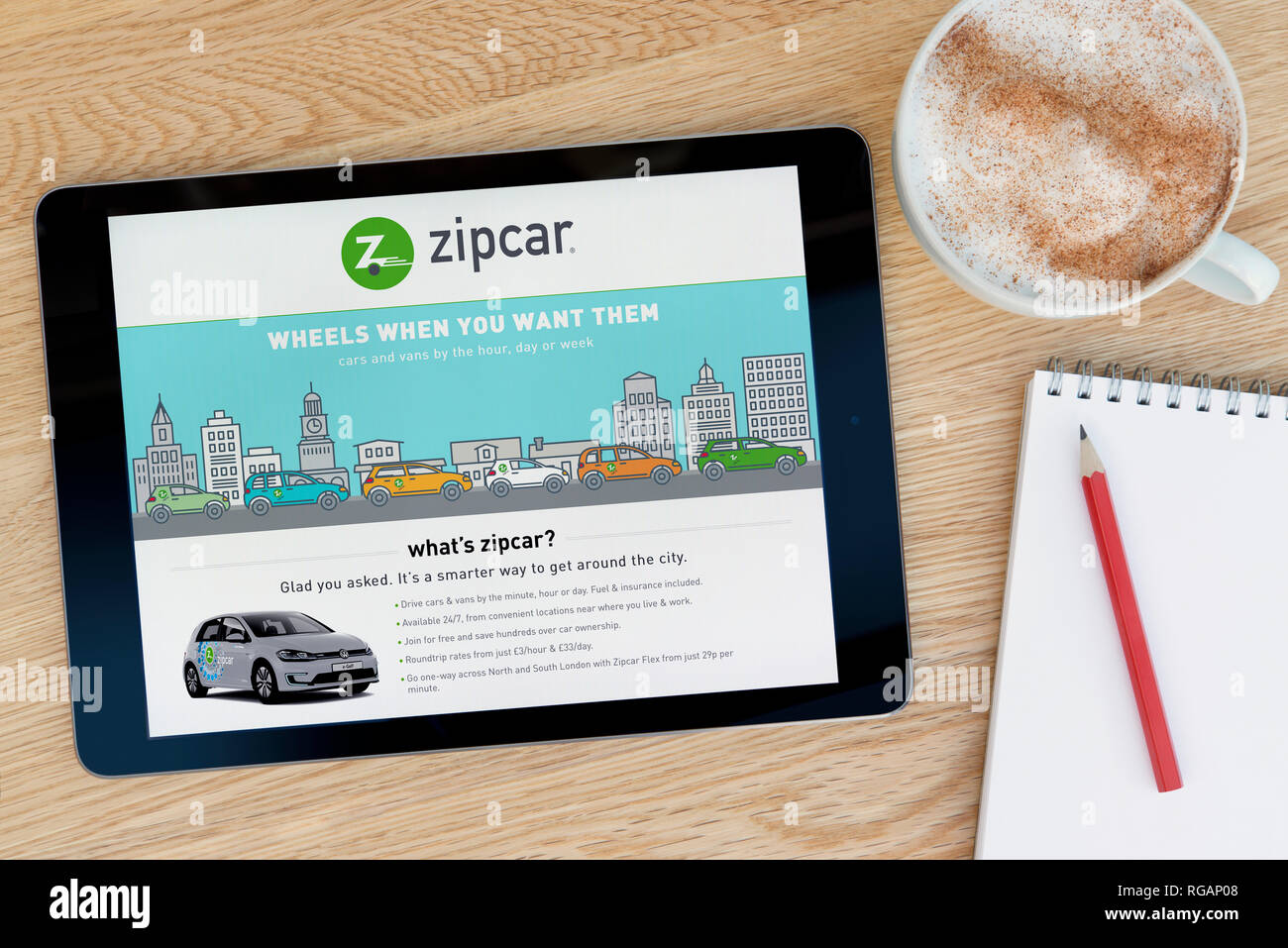 The Zipcar website features on an iPad tablet device which rests on a wooden table beside a notepad (Editorial use only). - Stock Image