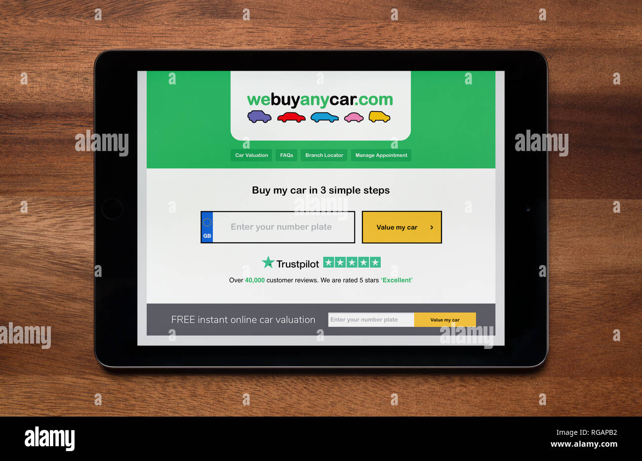 The website of We Buy Any Car is seen on an iPad tablet, which is resting on a wooden table (Editorial use only). - Stock Image