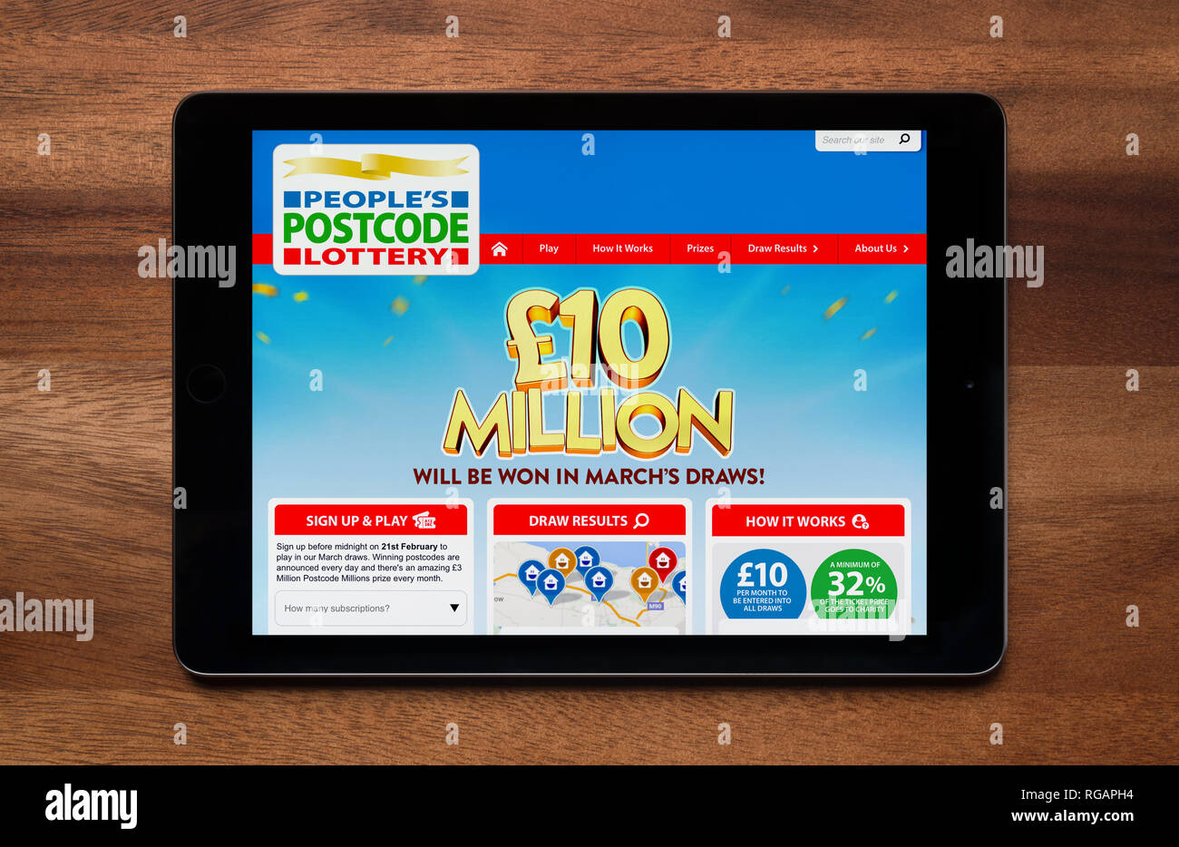 The website of People's Postcode Lottery is seen on an iPad tablet, which is resting on a wooden table (Editorial use only). - Stock Image