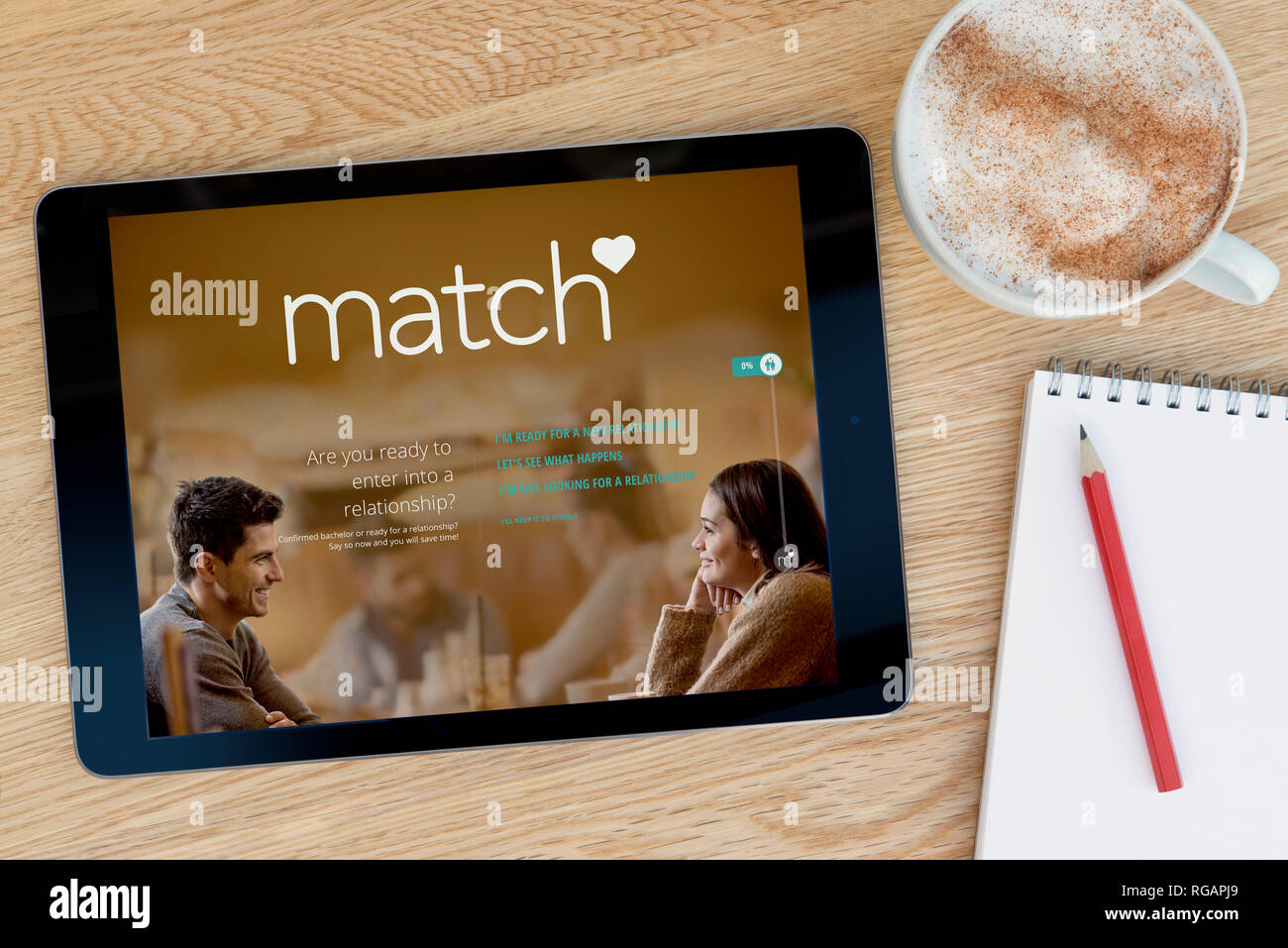 The Match.com website features on an iPad tablet device which rests on a wooden table beside a notepad (Editorial use only). - Stock Image