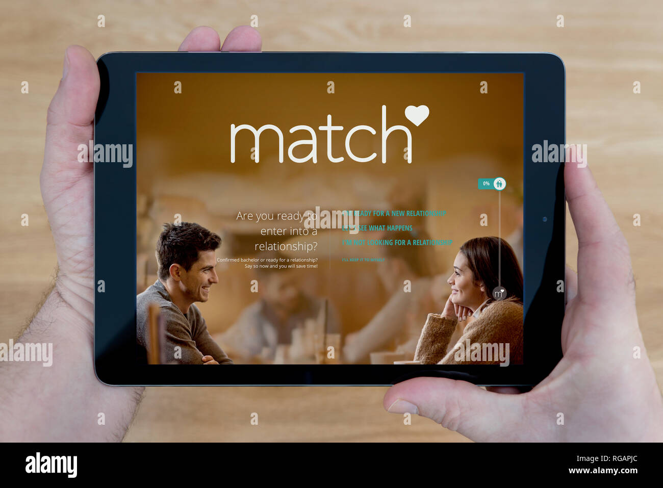 A man looks at the Match.com website on his iPad tablet device, shot against a wooden table top background (Editorial use only) - Stock Image