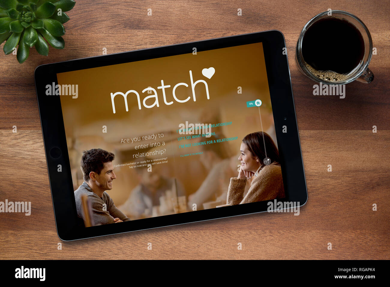 The website of Match.com is seen on an iPad tablet, on a wooden table along with an espresso coffee and a house plant (Editorial use only). - Stock Image