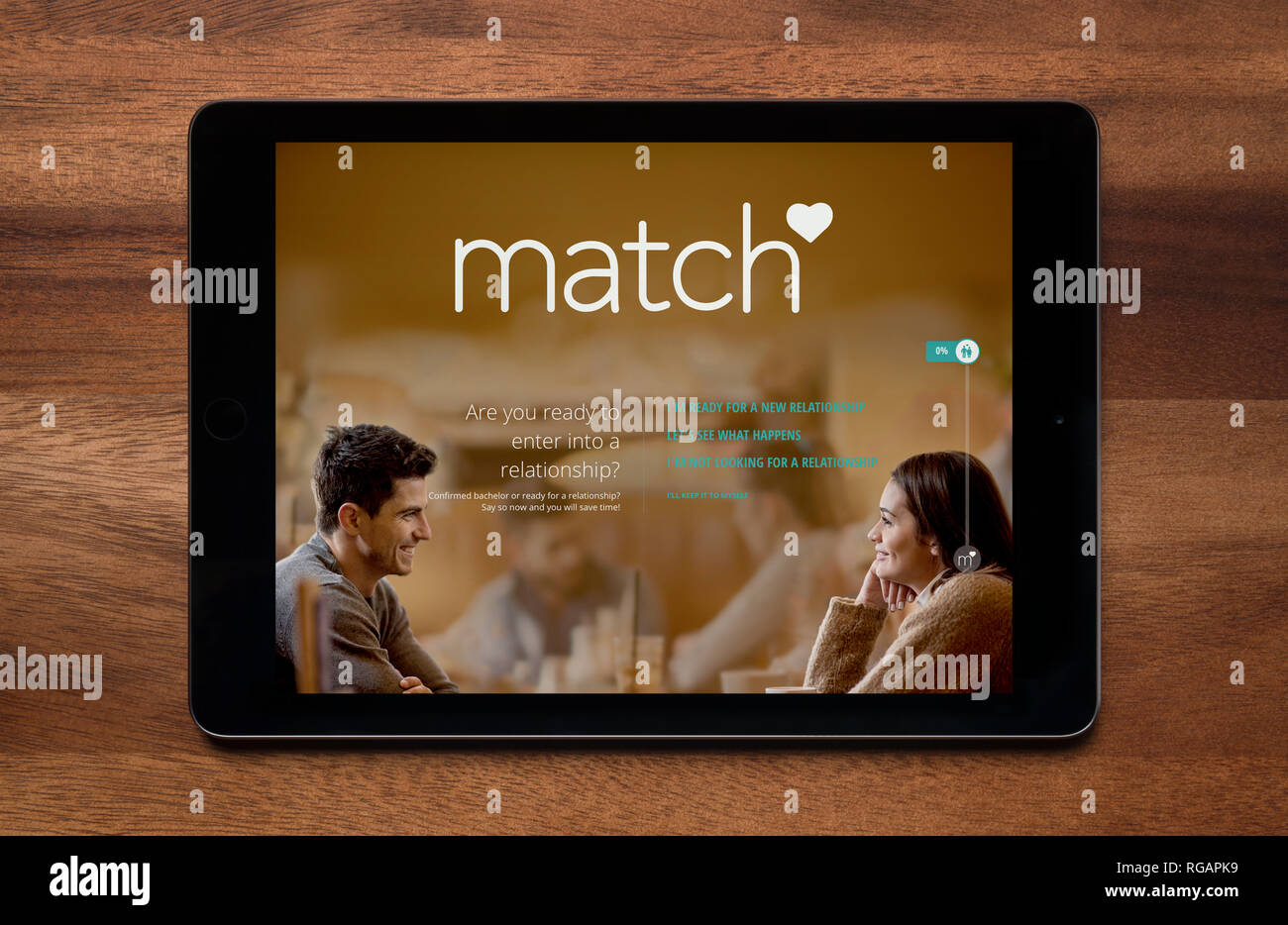 The website of Match.com is seen on an iPad tablet, which is resting on a wooden table (Editorial use only). - Stock Image