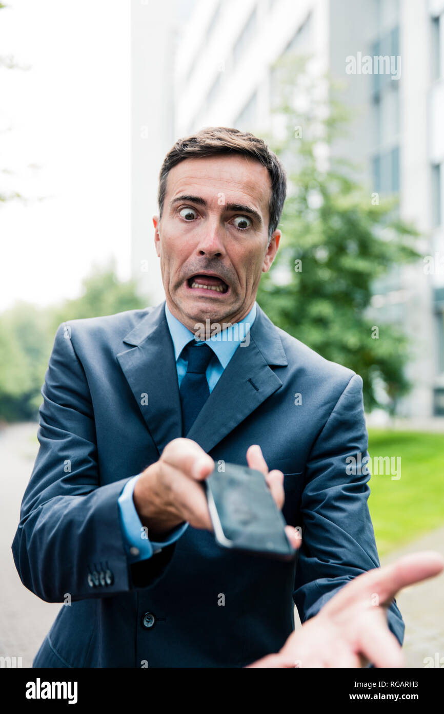 Shocked businessman with cell phone in the city - Stock Image
