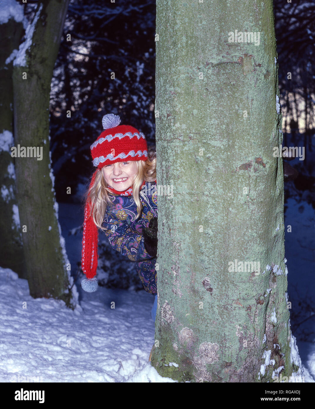 Young girl playing hide and seek in the snow. - Stock Image