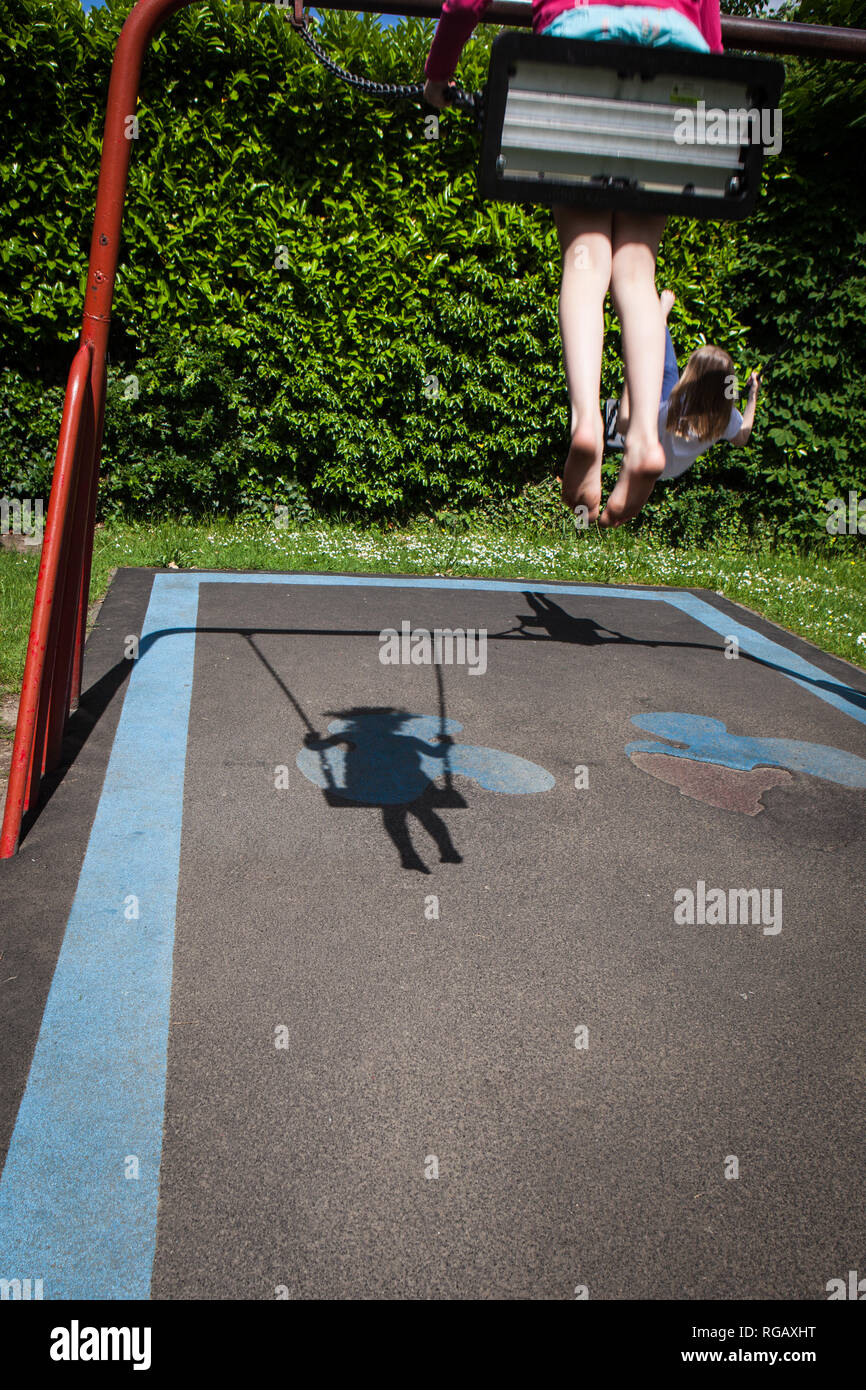 Two caucasion girls playing on swings in a park in a playground with shadow Stock Photo