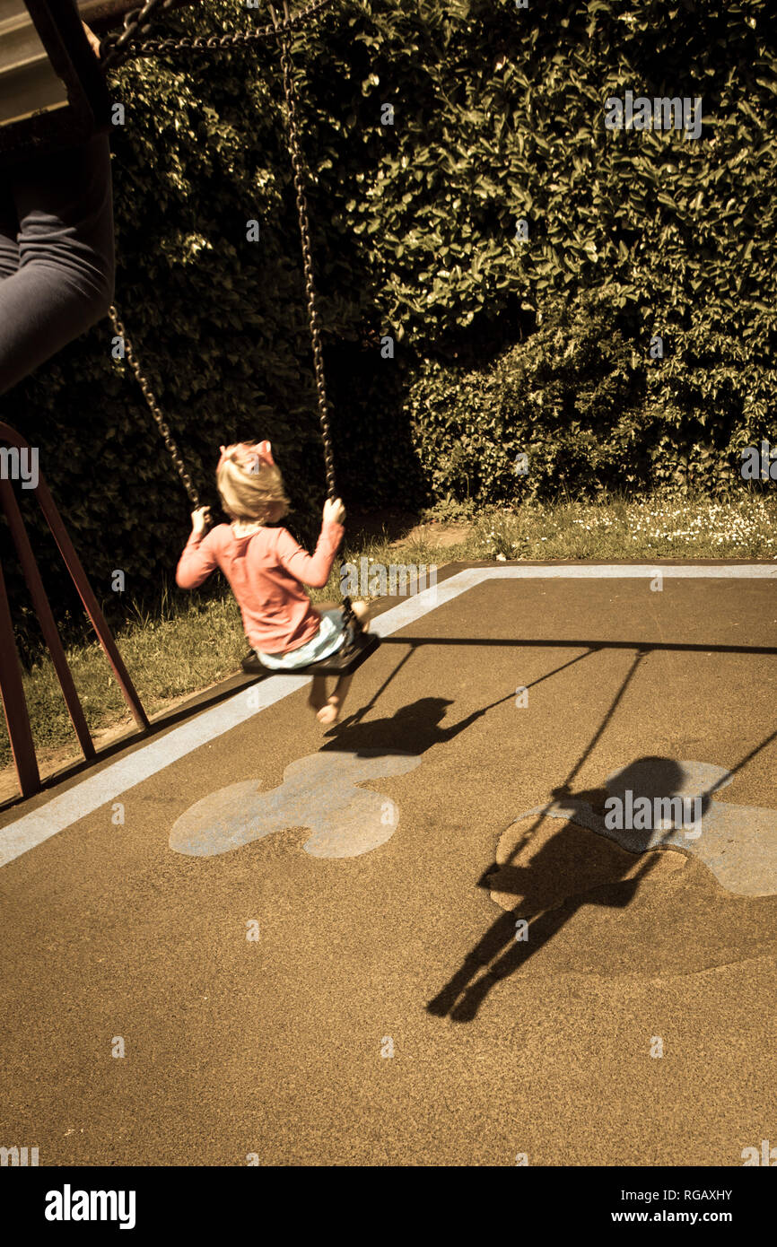 Two caucasion girls playing on swings in a park in a playground and shadows Stock Photo