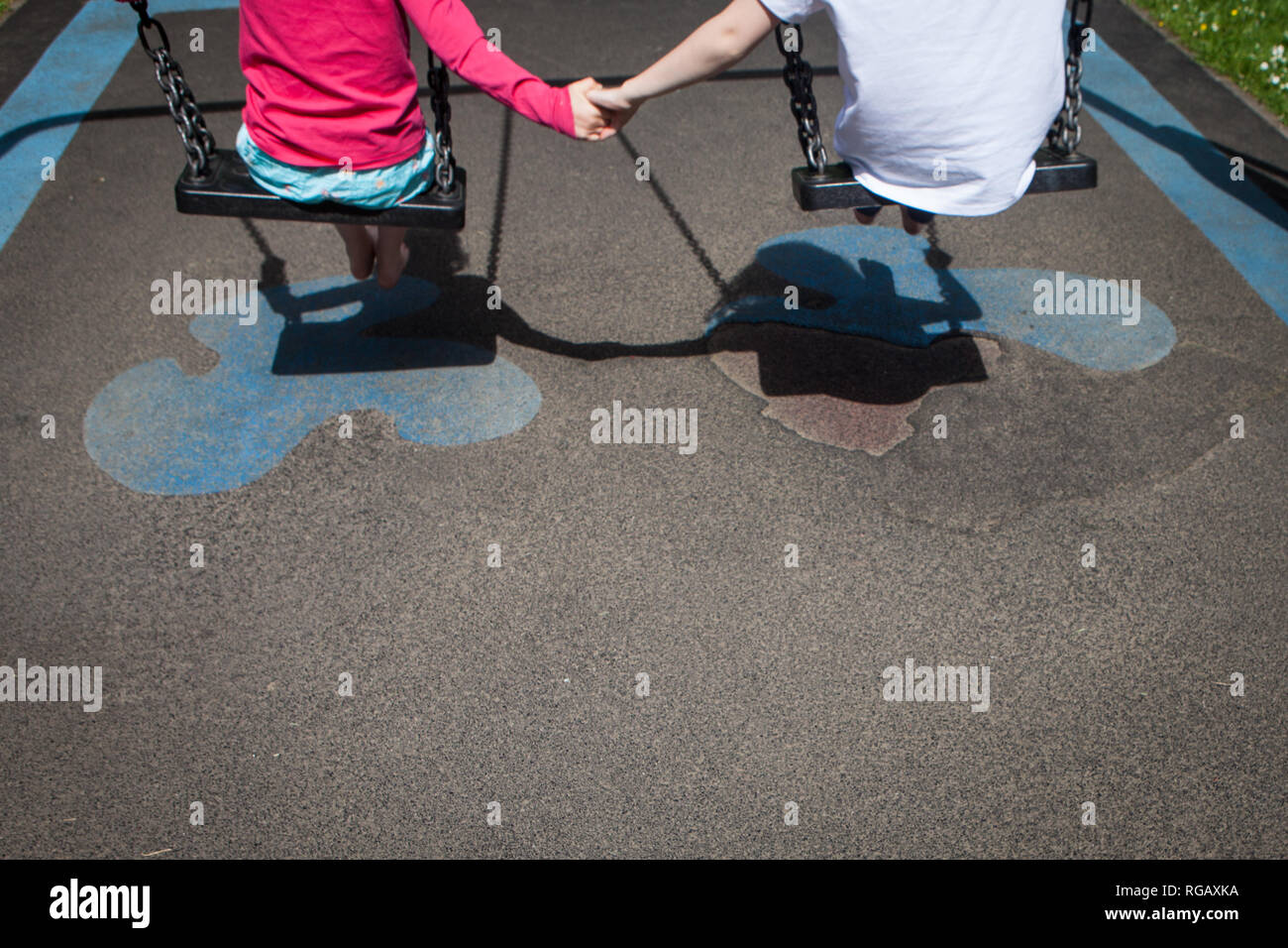 Two caucasion girls playing on swings in a park in a playground Stock Photo