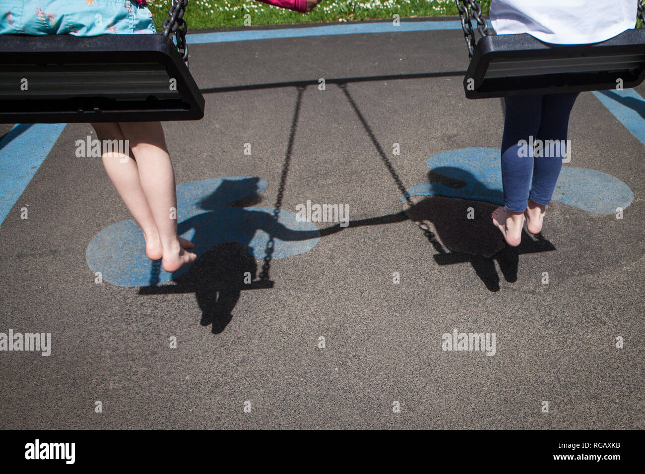 Shadow of two caucasion girls playing on swings in a park in a playground Stock Photo