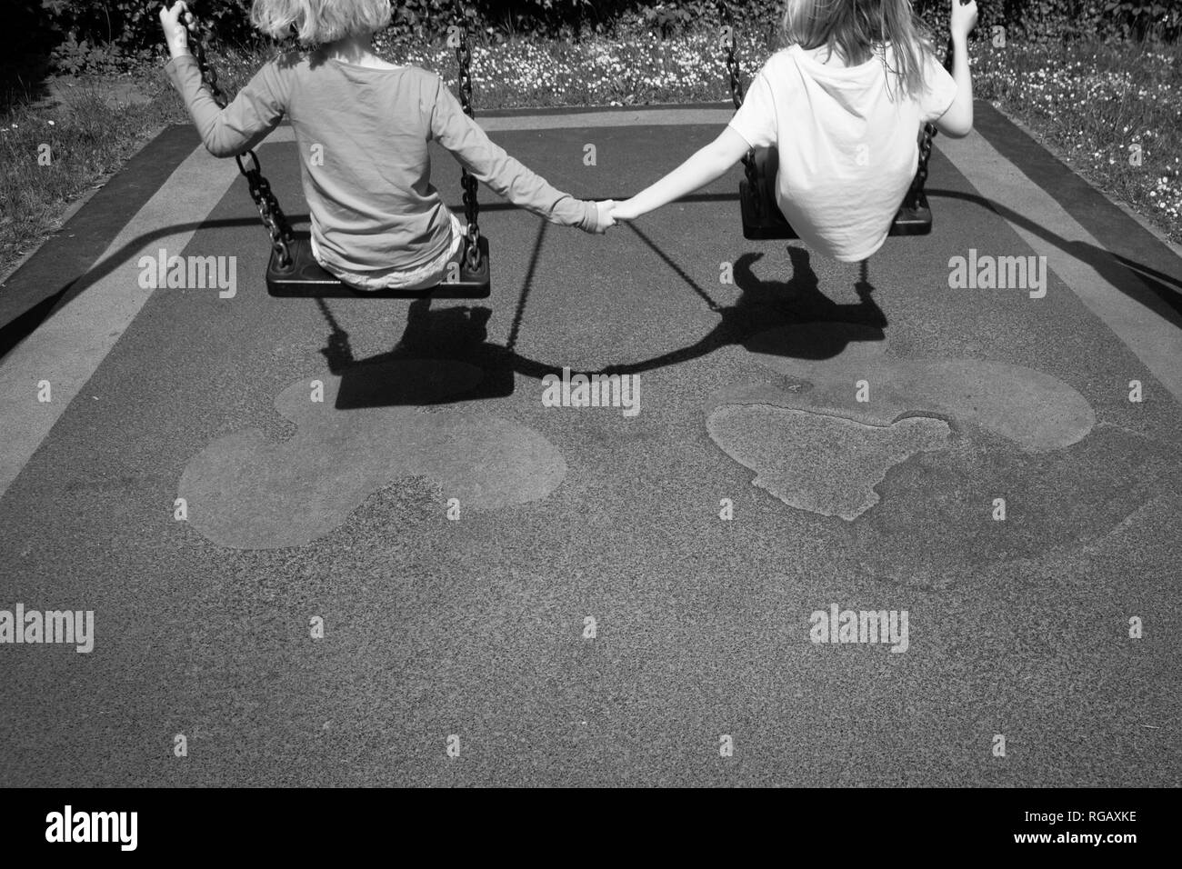 b;acl and white photograph of Two caucasion girls playing on swings in a park in a playground Stock Photo