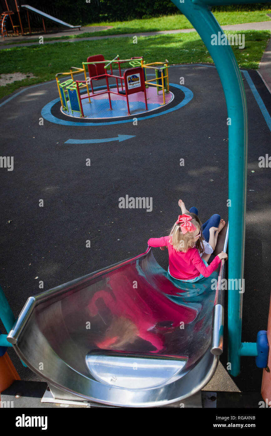 two caucasion girls on a slide in a playground Stock Photo