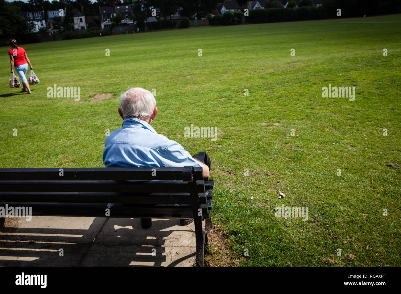 Old man on bench in a park looking at a woman with shopping in Summer Stock Photo