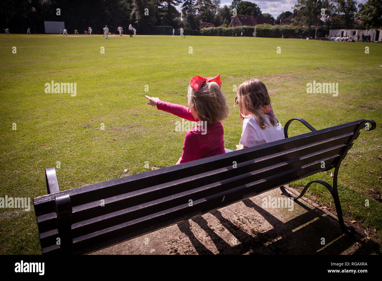 two young girls sitting on a park bench watching cricket Stock Photo