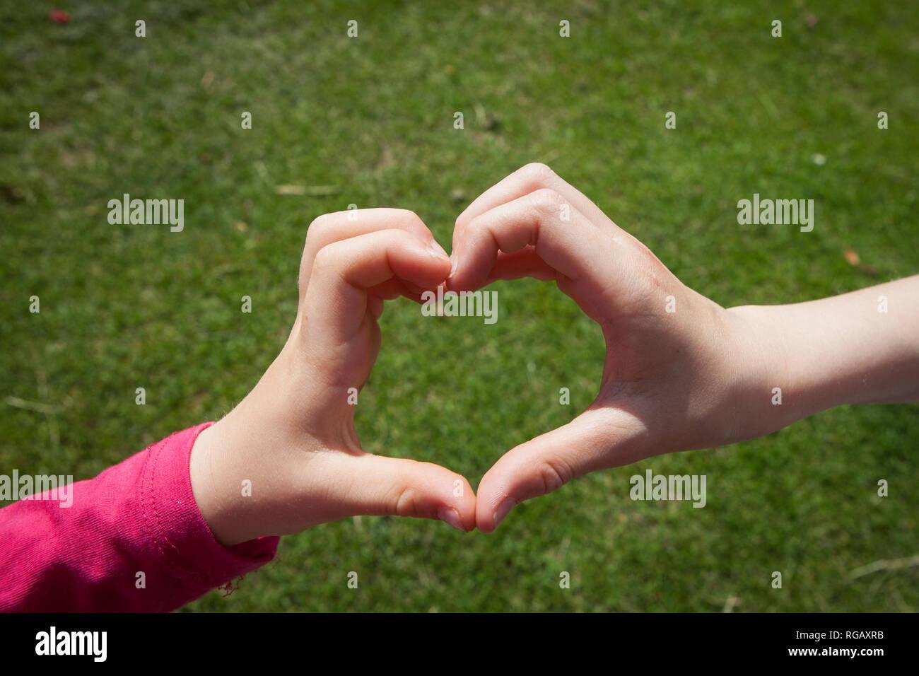 Children hands making a love heart sign above grass Stock Photo
