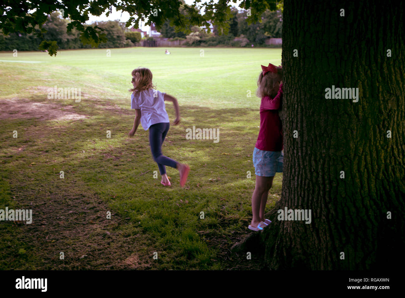 two young girls playing hide and seek in a park in Summer Stock Photo