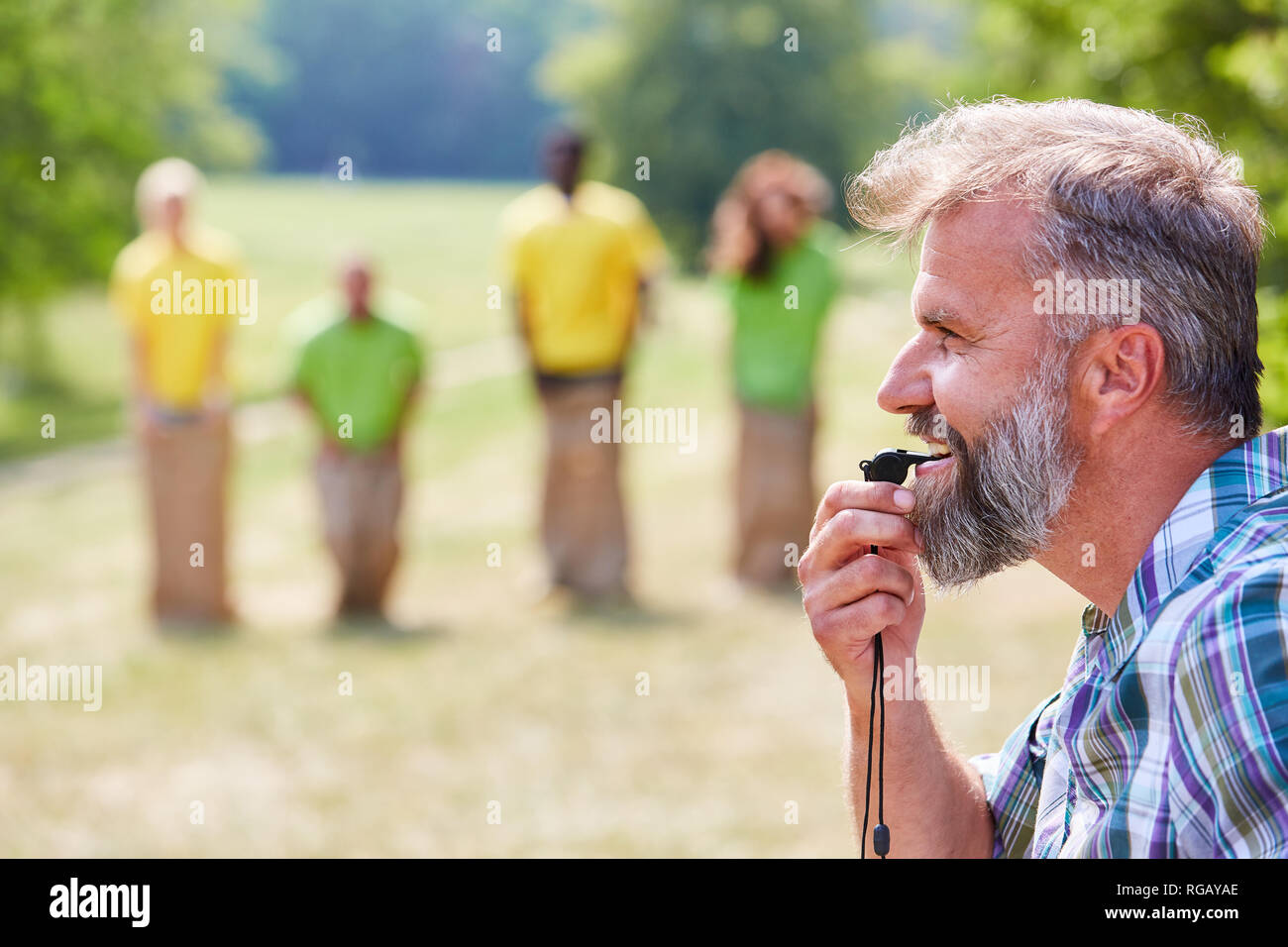 Referee with whistle at the start during sack races - Stock Image