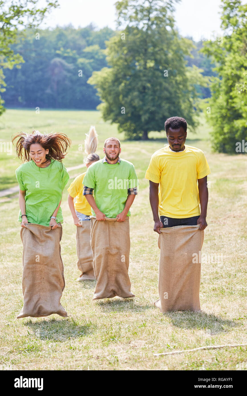 Young people in sack race competition at a teambuilding event - Stock Image