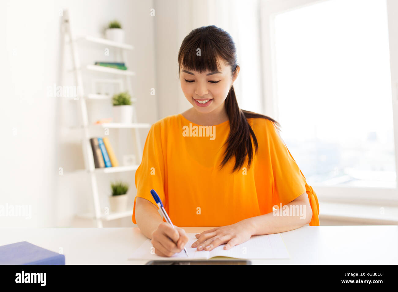 asian student girl writing to notebook at home - Stock Image